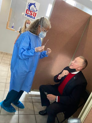 Colorado State University Pueblo President Timothy Mottet, (right) receives a COVID-19 test at the university's new testing site. The new site will run between 800-1,000 tests each week.
