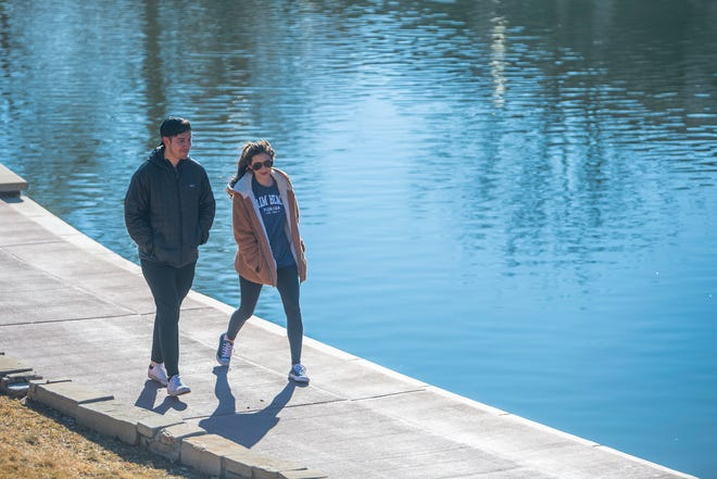 Brandon DeHerrera, left, and Emily Gordon take a stroll along the Riverwalk on Friday ahead of expected colder temperatures and possible snow this weekend