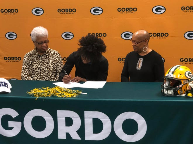 Hunter Oglen signs his letter of intent to play at Tennessee State while his mom and grandmother look on.
