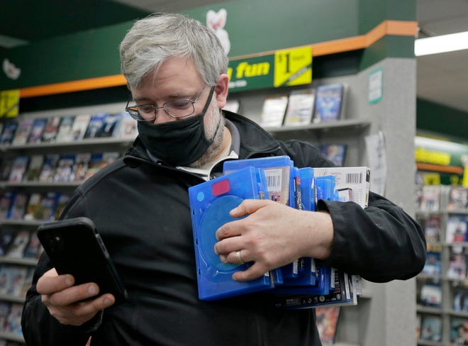 Andrew Raymond of Dublin checks a list on his phone for movie titles to add to his extensive collection at home, which, he said, was in the thousands.
