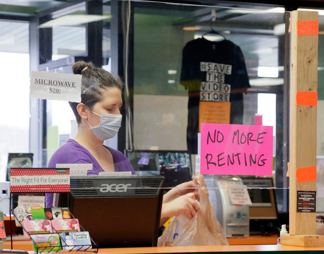 Family Video is closing its remaining locations in central Ohio, including the store at 2760 East Dublin-Granville Road in north Columbus. Store manager Demetra Fotis bags a customer's purchase from behind a plexiglass barrier Jan. 6.