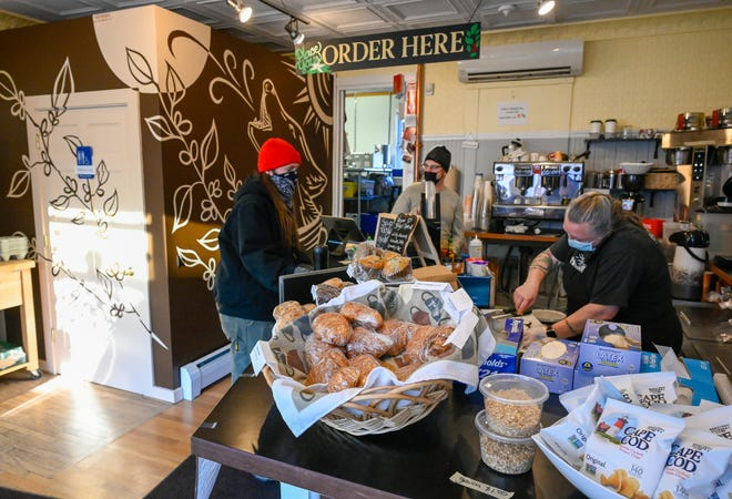 Diane Wolf, right, spreads cream cheese on a bagel for a customer inside Wolf Next Door Coffee on Derby Street in Salem which recently opened for business, Friday, Jan. 8, 2021.