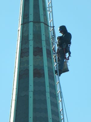 A worker is shown near the top of the steeple at the First Congregational Church in Natick on Jan. 8.
