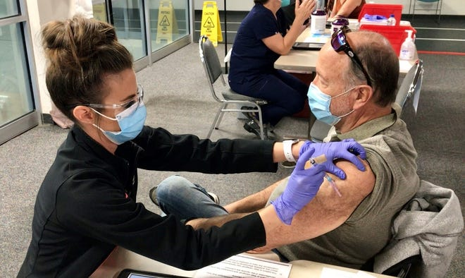 A man receives a COVID-19 vaccination Friday morning at the Health First Physical Therapy building in Melbourne.