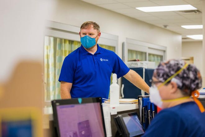 David Lee, chief executive officer at Otto Kaiser Memorial Hospital in Kenedy speaks with staff in the ER. Lee said they are are luckier than many to have the local H-E-B pharmacy and hospitals in Cuero and Floresville that were willing to help inoculate a few dozen workers at his hospital.
