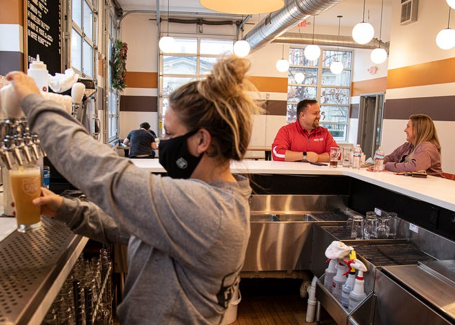 Mark and Krystal Disantis eat at the bar as bartender Miranda Riddle pours a bear at Fifty West Brewing Company in Downtown Chillicothe on Thursday, Jan. 7, 2020.