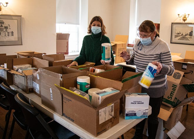 South Salem Village councilwomen Angie Page, left, and Vicki Smith, right, fill boxes with sanitary wipes and other personal protective equipment after receiving a grant from the state of Ohio to distribute to local households.