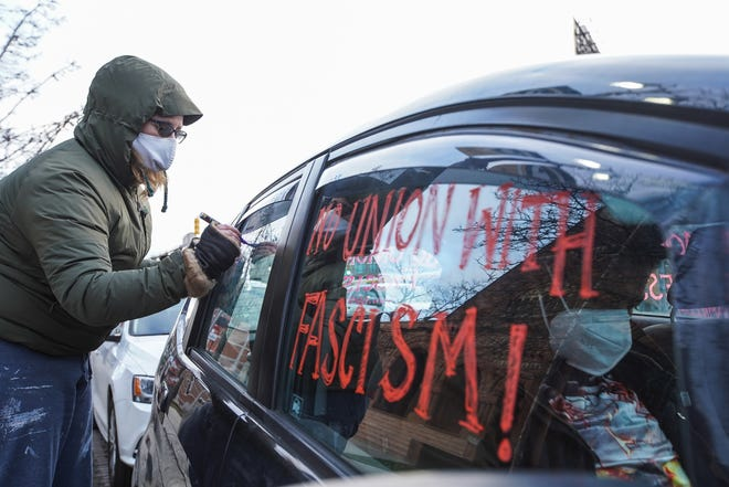 BAMN organizer Liana Mulholland writes messages on the windows of her vehicle before taking part in an emergency protest/car caravan organized by the group on Thursday, December 7, 2021 in Detroit while calling for the removal of President Trump.