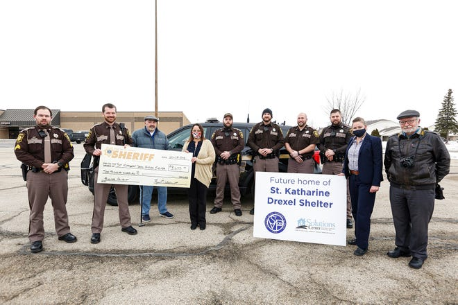 From left to right are Fond du Lac Sheriff's Department patrol deputy Alex Volm, Sheriff Ryan Waldschmidt, St. Vincent de Paul Vice President Bob Ramstack, Solutions Center's Amy Loof, sheriff depart members Bo Galligan, Jason Bruggink, Joseph Cole and Trevor Klemmer, Solutions Center's Kristina Meilahn and St. Vincent de Pauls President Bob Hartzheim. Doug Raflik/USA TODAY NETWORK-Wisconsin