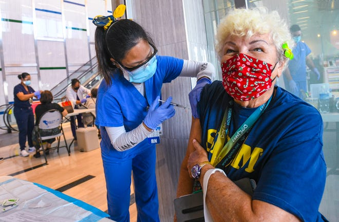 Yona resident Ginny Caceres, 70, draws a breath in as nurse Kristine Alba injects her with a dosage of mRNA-1273, more commonly known as the Moderna COVID-19 vaccine, during a vaccination held at Guam Regional Medical City in Dededo on Friday, Jan. 8, 2021.
