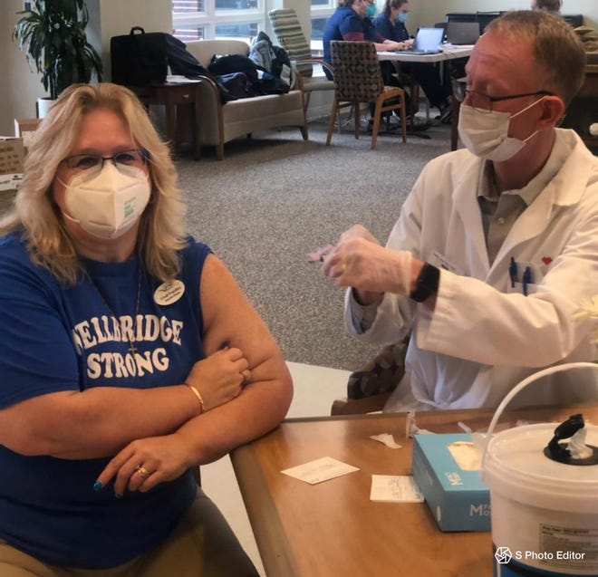 Registered nurse Joline Verellen receives her first dose of COVID-19 vaccine, Monday, Jan. 4, 2021, at WellBridge of Brighton, where she works.