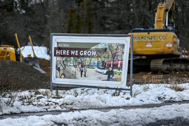 A sign for the development of the Village of Okemos is displayed in a construction lot on Thursday, Jan. 7, 2021, in downtown Okemos.