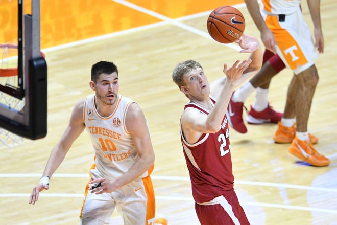 Arkansas forward Connor Vanover (23) reaches for the ball in front of Tennessee's John Fulkerson (10) on Wednesday in Knoxville, Tenn.