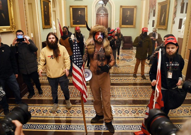 Jake Angeli with Trump followers in U.S. Capitol