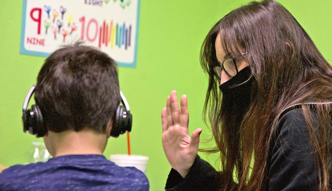 Lynsie Provost, right, offers a high-five while working with a student at the San Angelo Autism Center on Friday, Jan. 8, 2021.