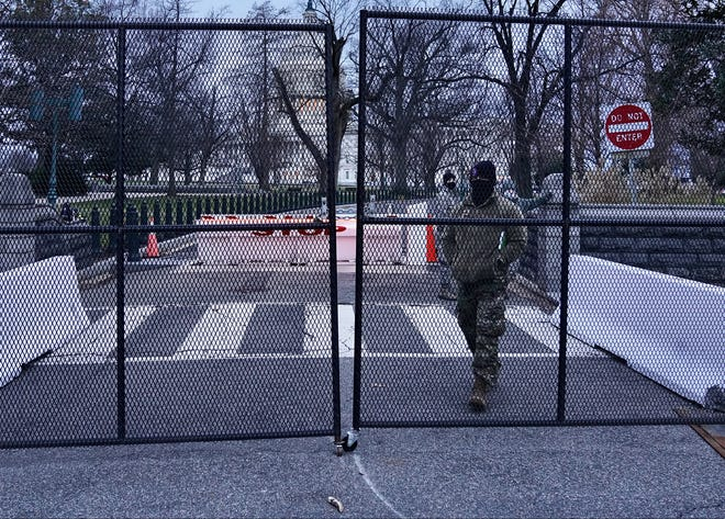Unarmed members of the National Guard stand watch Friday inside new metal fencing erected around the U.S. Capitol building in Washington two days after an attack by pro-Trump supporters.