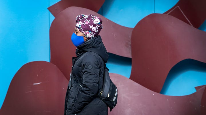 A woman wearing a face mask to protect against the coronavirus walks along 9th & Locust Street, during a cold day in Philadelphia., Jan. 6, 2021.
