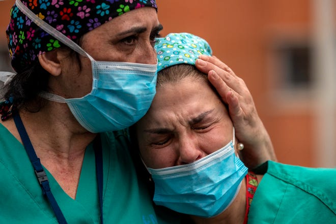 Health workers cry during a memorial for their co-worker who died from COVID-19 on April 10, 2020.