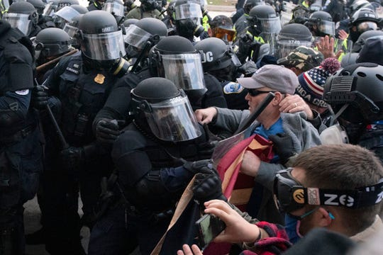 Capitol police officers in riot gear push back demonstrators who try to break a door of the Capitol on  Jan. 6, 2021, in Washington.