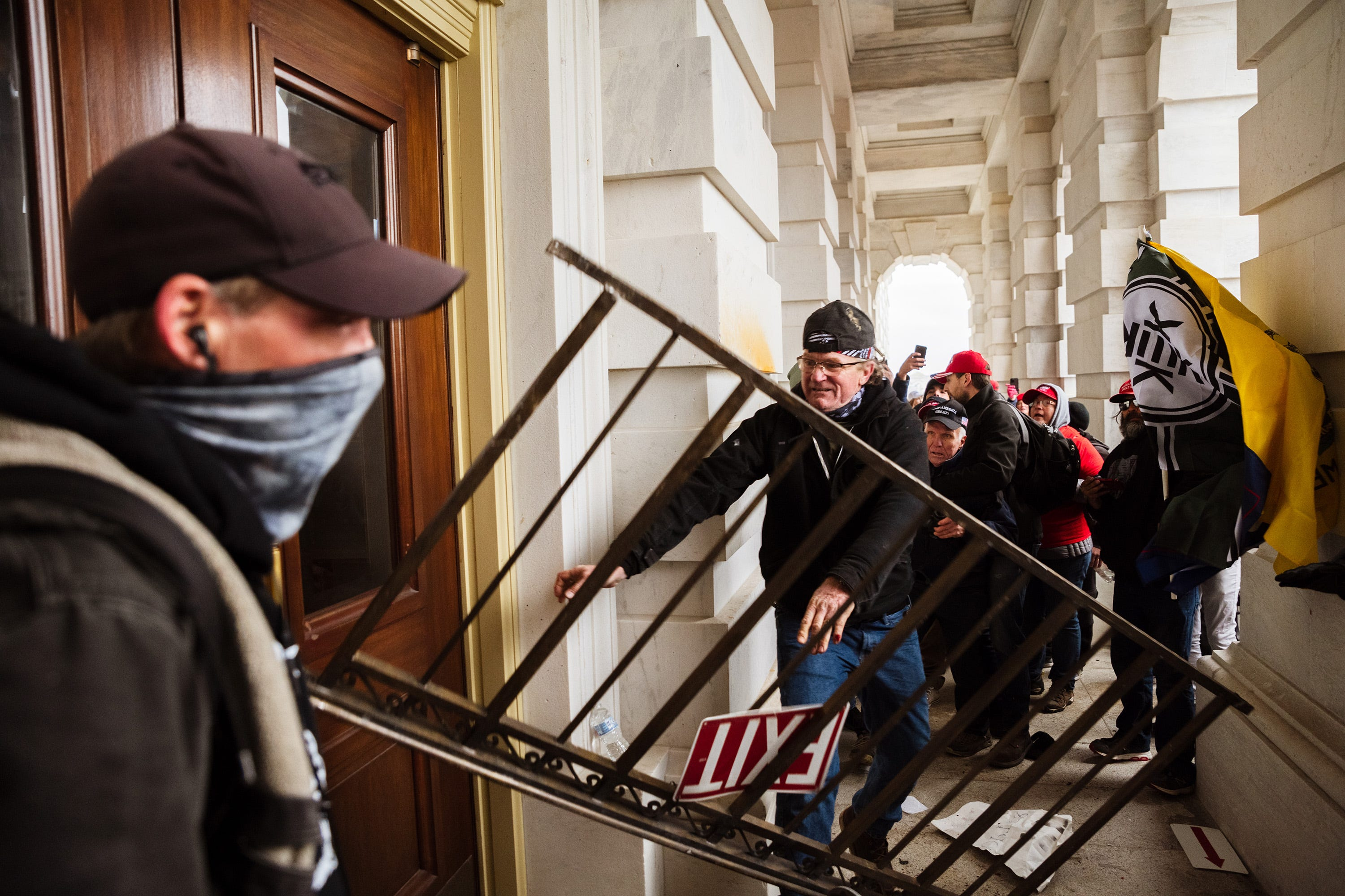 A rioter uses railing to bash a door at the Capitol as others stand by filming his attempt to gain access to the building.