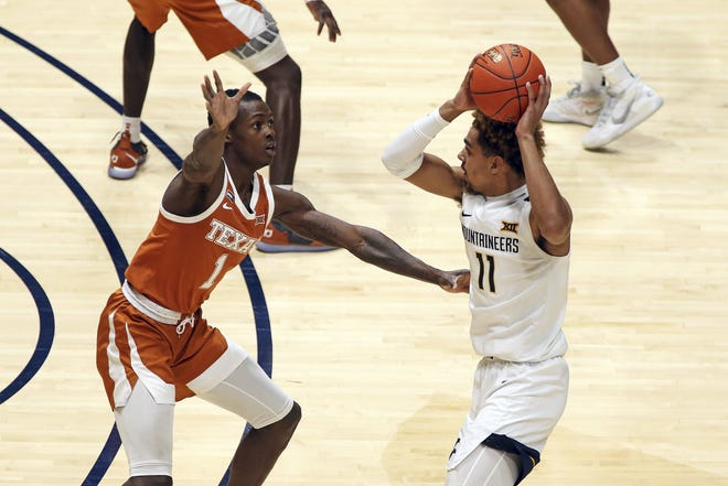 West Virginia forward Emmitt Matthews Jr. (11) passes while being defended by Texas guard Andrew Jones (1) during their game Saturday in Morgantown, W.Va. Jones hit the winning shot three years to the day of the announcement of his cancer diagnosis.