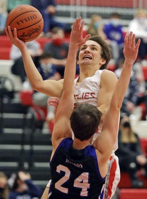 Wadsworth's Alex Risher, top, makes a layup over Hudson's JD Taylor during the first half of a basketball game, Friday, Jan. 8, 2021, in Wadsworth, Ohio. [Jeff Lange/Beacon Journal]