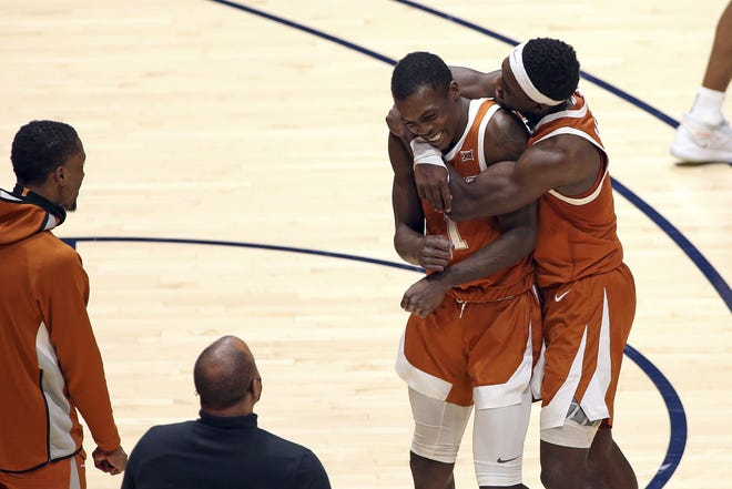 Texas guards Andrew Jones (1) and Courtney Ramey (3) celebrate after Jones hit the decisive shot in a 72-70 win over West Virginia on Saturday in Morgantown, W.Va. Ranked fourth in the AP poll, Texas has won six straight games.