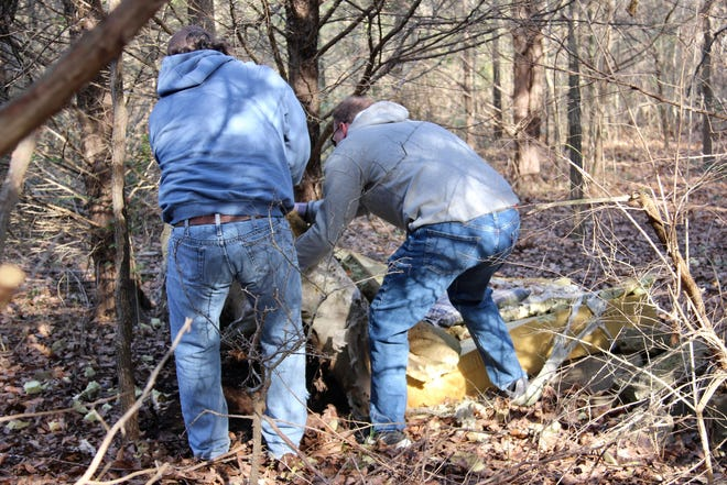 Ardmore Clean Team members remove a mattress found at a homeless camp in a wooded area behind the Ardmore Veterans Center.