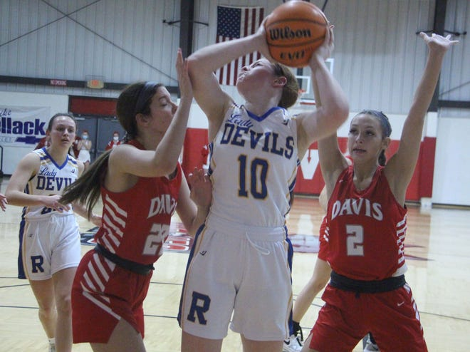 Davis' Elisabeth Adams, left, and Chloe Summers (2) defend Ringling's Sarah Southward as she attempts a shot on Friday night. The Lady Wolves cruised to a 50-14 win to advance to the title game of the Arbuckle Winter Classic.