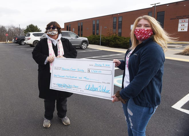American Cancer Society representative Nancy Verderber, left, receives a check from South Side Area High School student Chelsea Weber on Friday at the high school.   Weber raised $1,500 for breast cancer awareness by selling T-shirts and masks that she and her mother made.