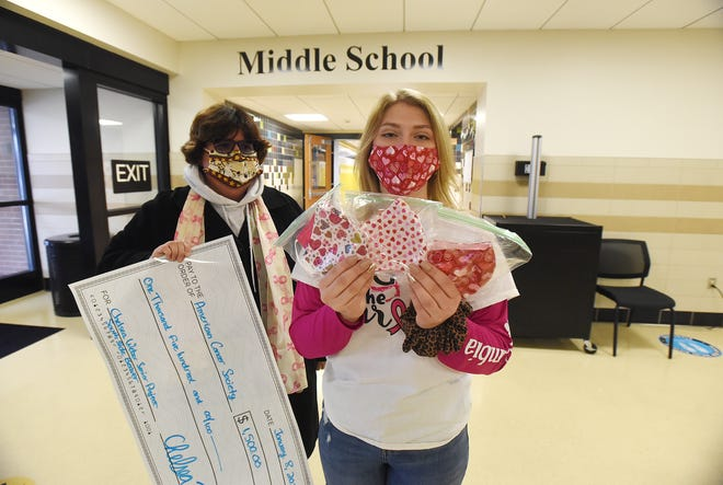 American Cancer Society representative Nancy Verderber, left, receives a check from South Side Area High School student Chelsea Weber on Friday at the high school.   Weber, holding masks, raised $1,500 for breast cancer awareness by selling T-shirts and masks that she and her mother made.