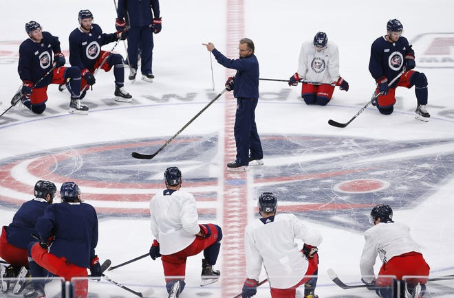 Blue Jackets coach John Tortorella, center, knows his team will have to be flexible and resilient this season in the face of NHL protocols relating to COVID-19, which prevented 17 of his players from practicing on Friday.
