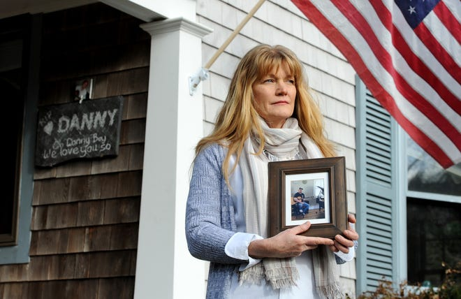 Susan Kinnane holds a photo of her son, Danny Vigliano, who died last year of a fentanyl overdose. She is standing at the memorial for him at her home. It includes the American flag that was folded in a military-style and was in his backpack.