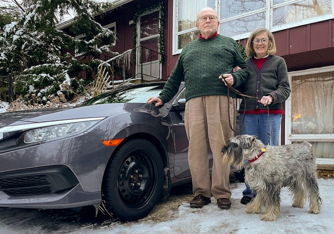 John and Dorothy Pazereskis pose for a photo with their dog Tommy in front of their home at 3566 W. Lake Storey Rd., just across from the Lake Storey dam, on Jan. 8, 2021.