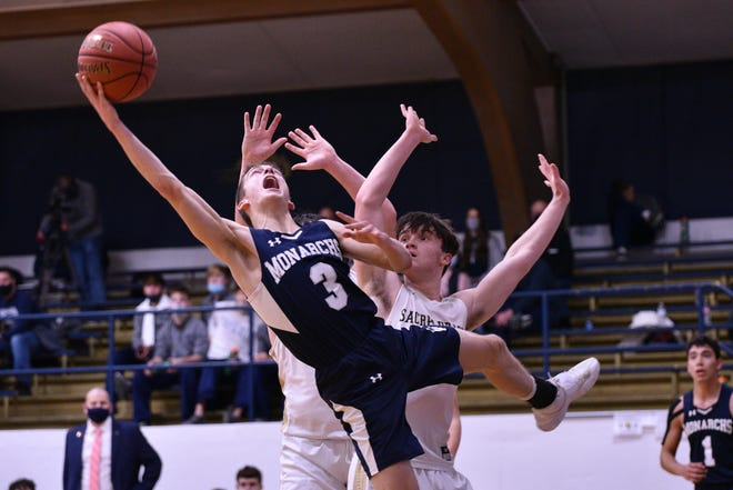 Hayden Brown (3) of TMP-Marian puts a shot up as he stumbles over Jacob Gormley (1) Sacred Heart on Friday night.  The Monarchs took home the road win with a final score of 54-47.