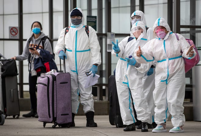 People wearing protective face masks, goggles and Tyvek suits, who said they traveled from Colombia wait for a car rental company shuttle, after arriving at Vancouver International Airport in Richmond, British Columbia., on Dec. 31. Beginning January 7, air travelers arriving in Canada will be required to provide proof of a negative COVID-19 test conducted within 72 hours of boarding the plane.