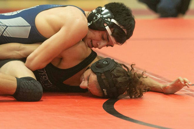 McKeel Academy's Jean Benavidez, top, wrestles with Tenoroc's Brandon Coleman during their 126-pound championship match during the 1A, District 11 wrestling tournament at Discovery High School.