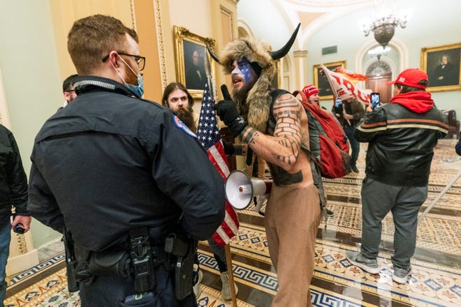Jacob Anthony Chansley, also known as Jake Angeli, in fur hat with horns, is among the Trump supporters confronted by U.S. Capitol police officers during Wednesday's siege at the U.S. Capitol. Angeli was taken into custody on Saturday.