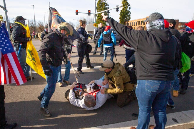 Fellow protesters and Eugene Police come to the aid of a man and his service dog after he was allegedly pushed to the ground by a counter-protester during an anti-socialism rally at the Federal Courthouse in Eugene on Saturday.