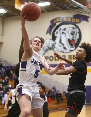 """Ben Sullivan (5) of Jackson drives to the basket while being guarded by Ronnell """"Tae"""" Perie (right) of McKinley during their game at Jackson on Friday, Jan. 8, 2021."""