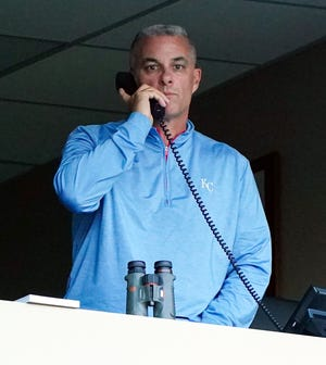 Kansas City Royals general manager Dayton Moore talks on the phone before a game last September at Kauffman Stadium in Kansas City.