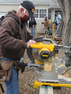 Salina Breakfast Bandit Ambucs member Kenny DuBois makes a cut on the chop saw as other members work on building the 400th handicap ramp the club has built for community members with disabilites.