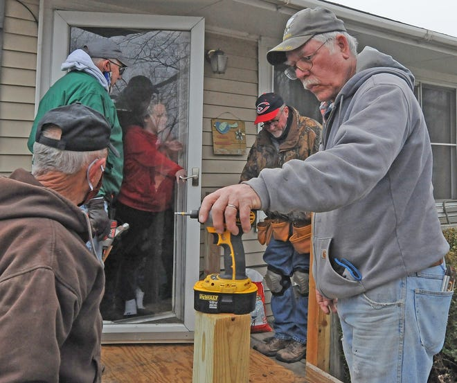 Shannon Meade visits with Salina Breakfast Bandit Ambucs members Kenny DuBois, from left, Don Merriman, Rob Pickrell and Jerry Base as they construct a handicap ramp for her mother Rhonda Blazek in Salina on Saturday morning.