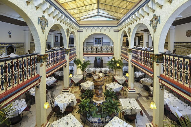 The Patio Dining Room, a grand space with a balcony that wraps around a double-height space, putting diners on two levels at the original Columbia Restaurant in Ybor City. That part of the building was constructed in 1937 under the direction of Casimiro Hernandez Jr., who became the owner when his father died in 1930. He worked with architect Iv de Minicis of Rimini, Italy.