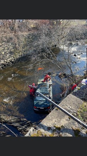 Emergency crews work to rescue a trapped driver from the Five Mile River in Danielson on Saturday.