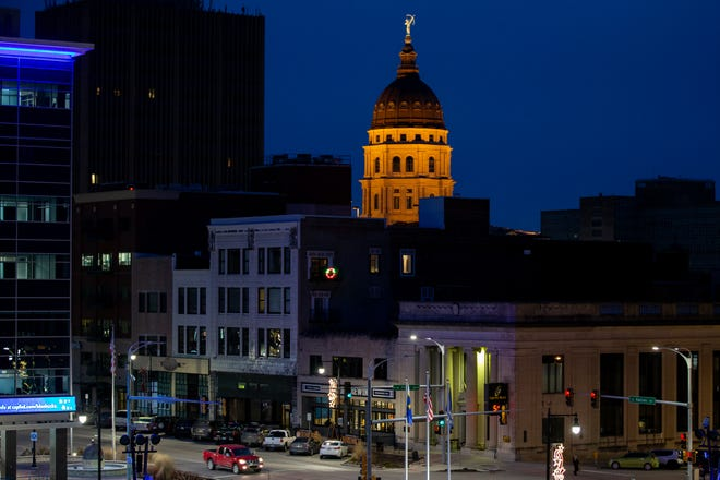 Businesses on Kansas Avenue show signs of life Friday evening as the Statehouse glows in the background. Downtown business owners hope to see an increase in customers in coming weeks and months as the Kansas Legislature convenes Monday.