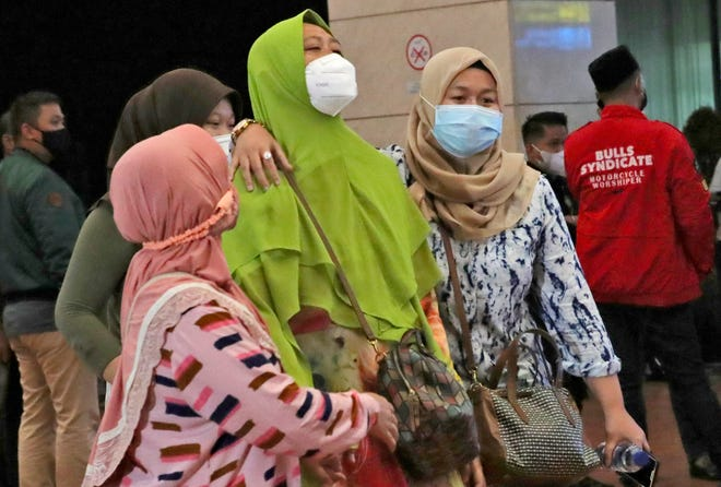Relatives of passengers arrive at a crisis center set up following a report that a Sriwijaya Air passenger jet has lost contact with air traffic controllers shortly after takeoff Saturday at Soekarno-Hatta International Airport in Tangerang, Indonesia.