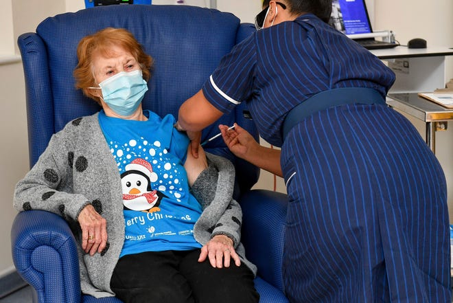 In this Dec. 8, 2020, file photo, 90 year old Margaret Keenan, the first patient in the UK to receive the Pfizer-BioNTech COVID-19 vaccine, administered by nurse May Parsons at University Hospital, Coventry, England.
