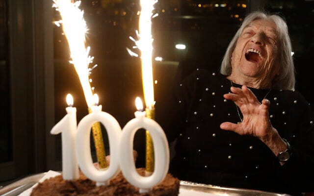 Agnes Keleti, former Olympic gold medal winning gymnast, reacts to fireworks going off on her birthday cake.