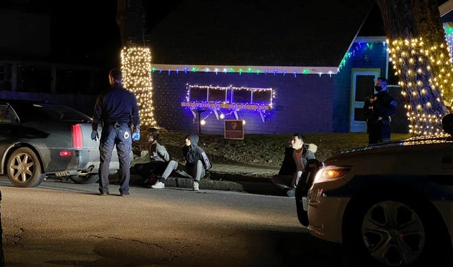 Police investigating an incident in which a shot was fired at a home in Worcester late Friday night, stand on Haviland Street near a Cadillac they stopped in connection with the shooting. Three people sit nearby in handcuffs on the sidewalk.